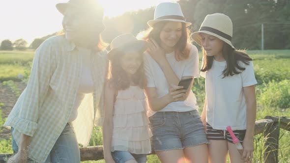 Thumbnail for Happy Mother with Three Daughters Looking in Smartphone, Family in Nature