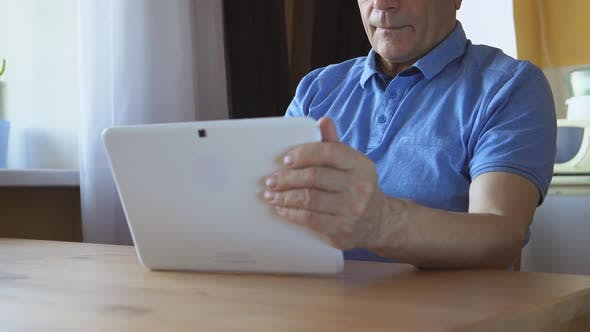 Thumbnail for Aged Male Sits And Uses A White Tablet Pc At Home