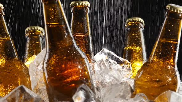 Thumbnail for Beer Stands in the Ice, Water Flows From Above, Splashes Fall on the Glass, Black Background