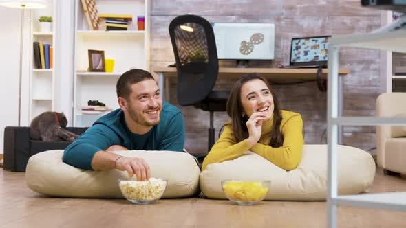 Thumbnail for Cheerful Couple Watching Tv Sitting on Pillows