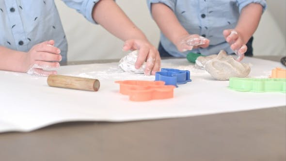 Thumbnail for Two boys preparing dough for cookies together with their mum