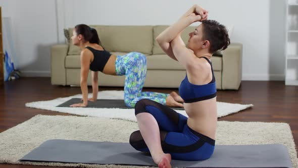 Cover Image for Woman Doing Cow Face Pose during Home Yoga Practice with Friend