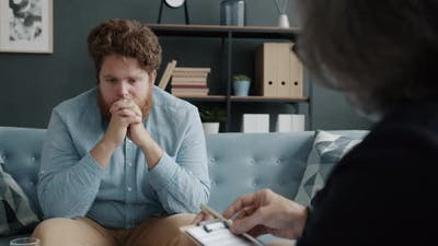 Worried and Sad Man Receiving Psychological Treatment in Therapist's Office