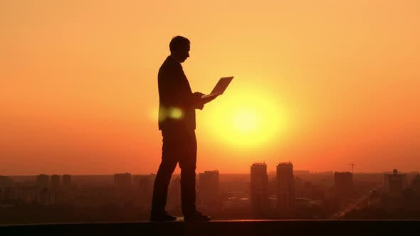 Man with Laptp Outdoors Cityscape at Sunrise