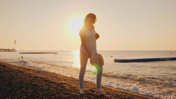 Thumbnail for A Happy Woman Walks Carefree Along the Surf Line, the Sun Rises Over the Sea. Holiday and Vacation