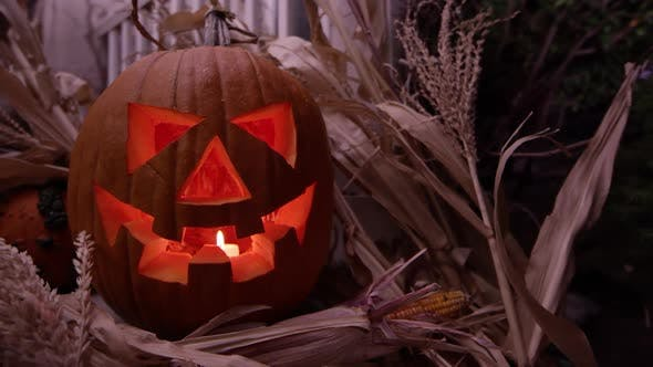 Thumbnail for Rotating view of jack o'lantern on porch as candle light flickers