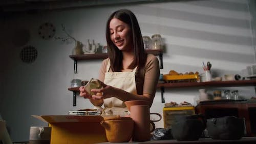 A young Asian woman ceramist is packing ceramic mugs in a parcel box for people who buy online.