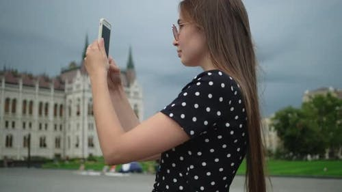 Girl Taking Smartphone Pictures of Hungarian Parliament Building in Budapest