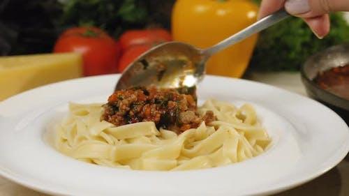 Adding Bolognese Sauce on Pasta Tagliatelle