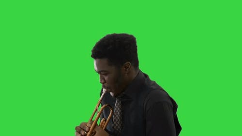 African American Musician Playing the Trumpet Expressively on a Green Screen, Chroma Key.