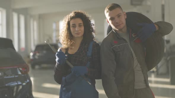 Thumbnail for Slowmo of Confident Male and Female Auto Mechanics Standing in Sunrays and Looking at Camera
