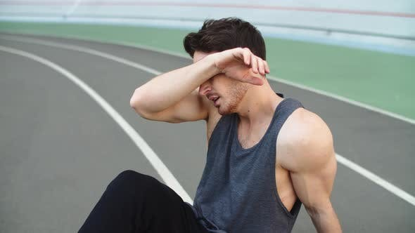 Thumbnail for Close Up of Exhausted Man Sitting on Stadium Track. Sport Man Resting