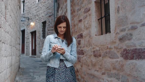 Thumbnail for Woman Using Smartphone in Old Town
