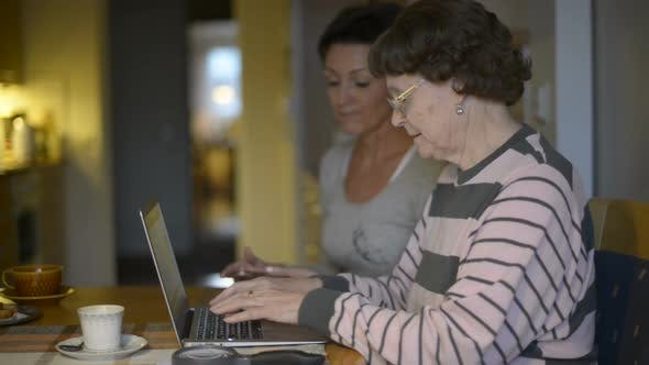 Frustrated Daughter Teaching Her Mother in Using Laptop at Home