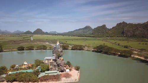 Aerial shot of the Kyauk Ka Lat Pagoda throning on a limestone pinnacle in Hpa-An, Myanmar