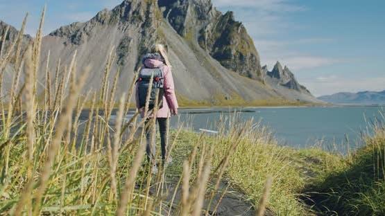 Morning Scene of Female Traveler Exploring Stokksnes Cape with Vestrahorn in Background