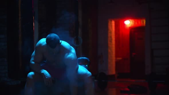 Tough Man Clapping His Hands Covered in Chalk and Pumping His Biceps in Contrast Lighting