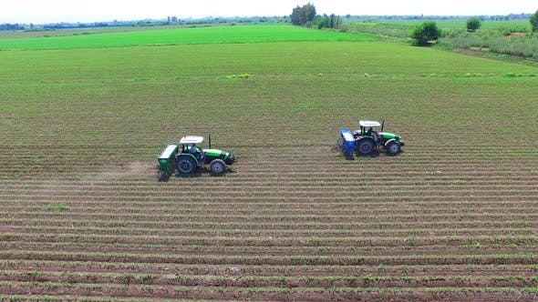 Tractors Pouring Fertilizer Into The Field