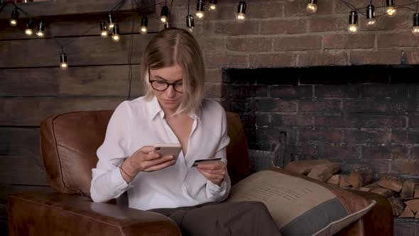 Smiling young woman customer holding credit card and smartphone sitting on couch at home