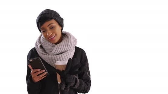 Cute black woman in her 20s texting on cellphone in studio with copyspace