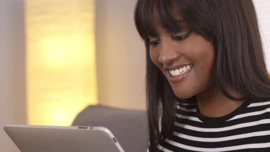 Cover Image for Happy black woman using tablet