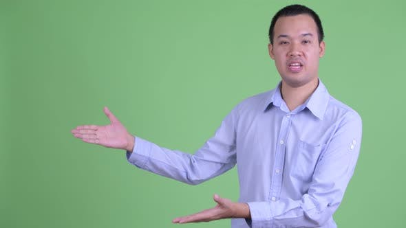 Thumbnail for Happy Asian Businessman Talking While Showing Something
