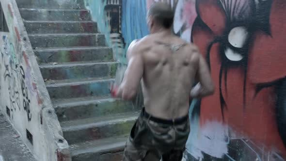 Thumbnail for A shirtless personal trainer man carries a concrete block up stairs
