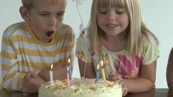 Thumbnail for CU OF A BROTHER AND SISTER BLOWING OUT CANDLES ON A BIRTHDAY CAKE