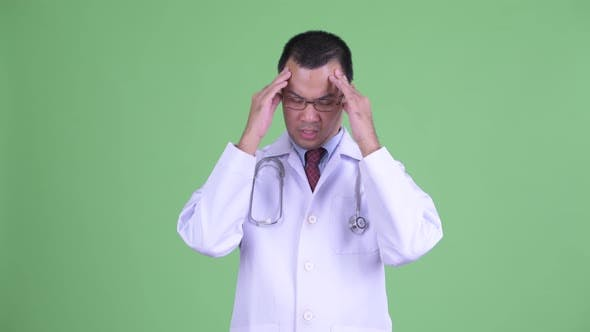 Thumbnail for Stressed Asian Man Doctor with Eyeglasses Having Headache