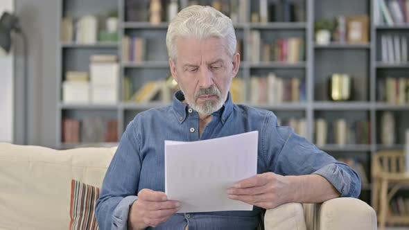 Old Man Reading Documents on Sofa