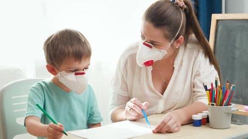 Kleiner Junge trägt medizinische Maske Atemschutzmaske Zeichnen oder Schreiben auf Papier, während er Hausaufgaben mit seinem macht
