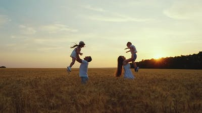 Parents Throwing Children Up in the Air in Field