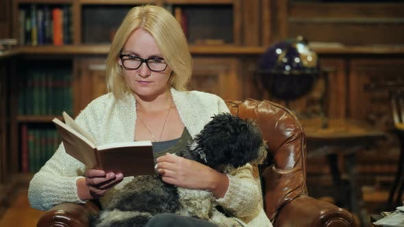 Thumbnail for A Woman Is Reading a Book in a Cozy Home Library in Her Arms Is a Small Dog