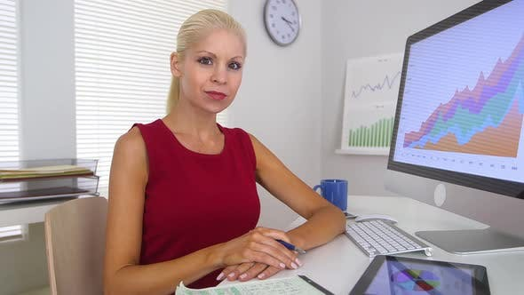 Cover Image for Blonde business woman smiling while sitting in front of computer