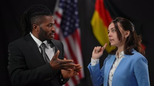 African American and Caucasian Diplomats Arguing at Press Conference with USA and German Flags at