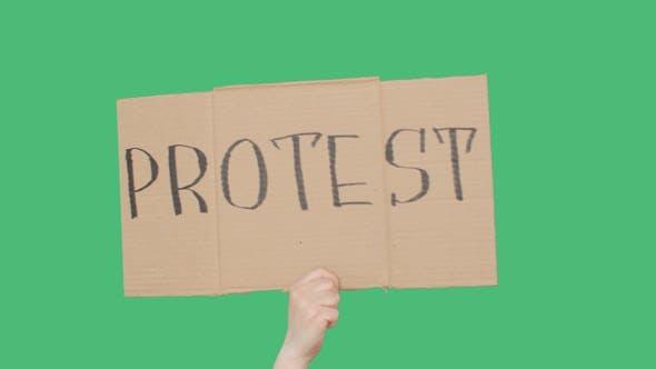 Thumbnail for Hand hält Karton mit Protestschild, grüner Chromakey-Hintergrund. Hand zeigt Protestkarton