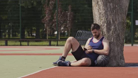 Young Basketball Player Checking Calories Consumption on Fitness Tracker