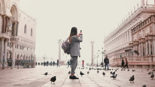 Thumbnail for Happy Female Tourist Taking Smartphone Photos on Amazing San Marco Square Full of Birds