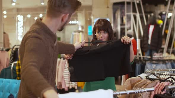 Thumbnail for Man Offers His Woman a Sweater and Shorts in a Store