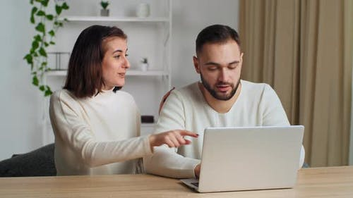 Young Caucasian Couple Spend Weekend at Home in Living Room Using Laptop Websurfing Searching