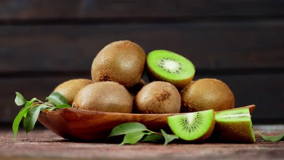Thumbnail for Aromatic Ripe Kiwi with Leaves on a Plate To Slowly Rotate