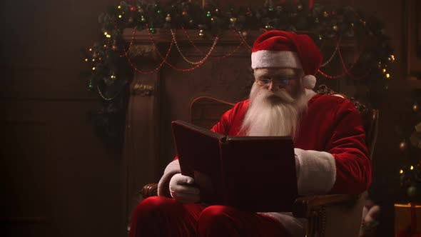 Thumbnail for A Beautiful Santa Claus Sitting in a Chair on the Background of a Decorated Christmas Tree with a