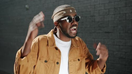 Talented African American Man Wearing Trendy Clothing and Sunglasses Singing and Gesturing