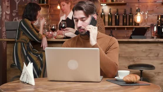 Thumbnail for A Handsome Young Businessman Talking on His Phone While Working in a Bar