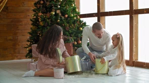 Thumbnail for Glückliche Familie sucht Geschenke über den Weihnachtsbaum am Feiertagsmorgen. Mod, Papa und zwei Tochter an
