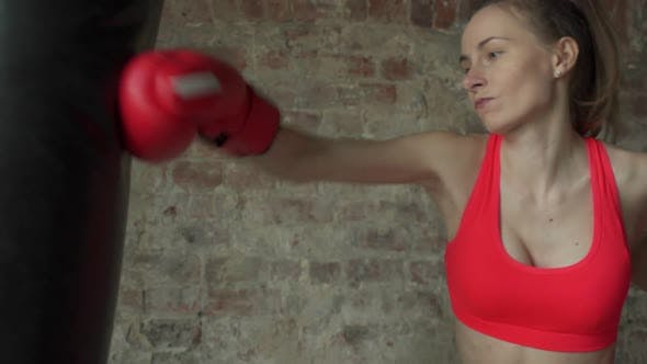 Boxer Young Female Beats Pear in a Modern Gym