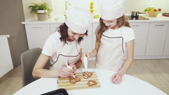 Thumbnail for Charming Mother and Cute Daughter Glazing Ginger Cookies