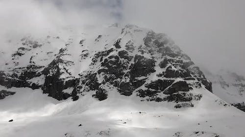 High Altitude Rocky Snowy Dome Mountain Peak in Cloudy Winter