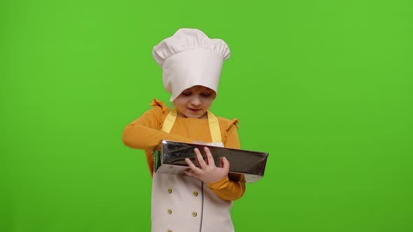Child Girl Cook Chef Baker in Apron and Hat Adding Raisins To Dough in Bowl Preparing Bread Cake