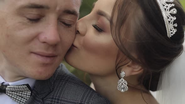 Thumbnail for Newlyweds. Caucasian Groom with Bride. Making a Kiss in Park. Happy Wedding Family Couple